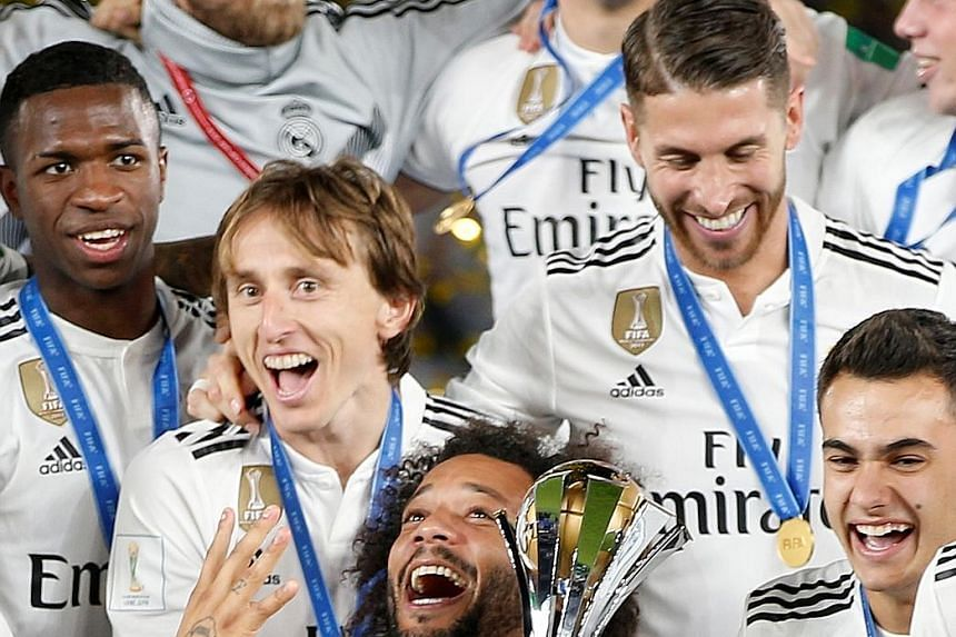Real Madrid players celebrating after winning the Fifa Club World Cup for a record fourth time in Abu Dhabi on Saturday.