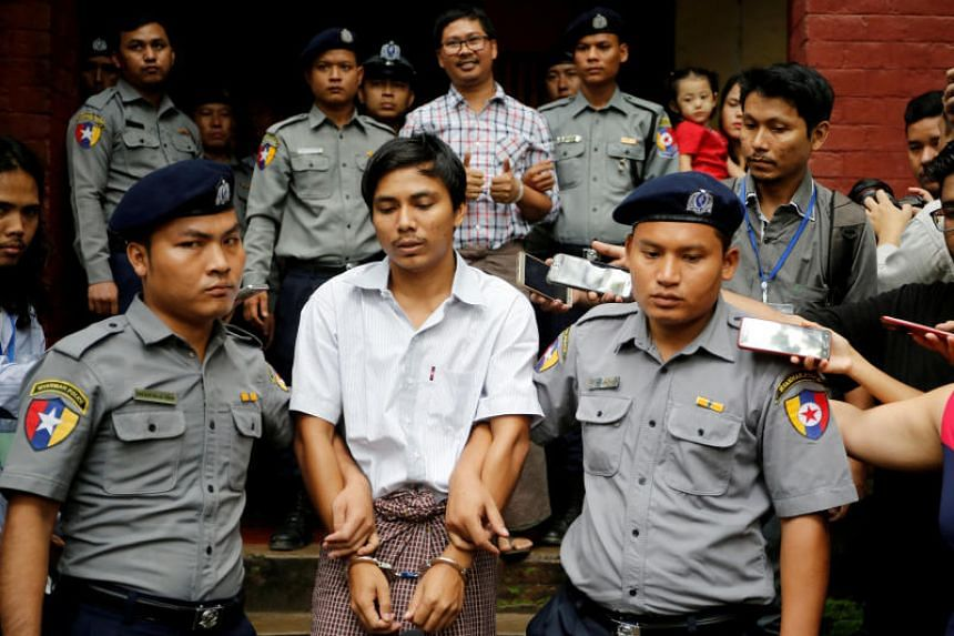 Detained Reuters journalist Kyaw Soe Oo and Wa Lone are escorted by police after a court hearing in Yangon, Myanmar, on Aug 20, 2018.