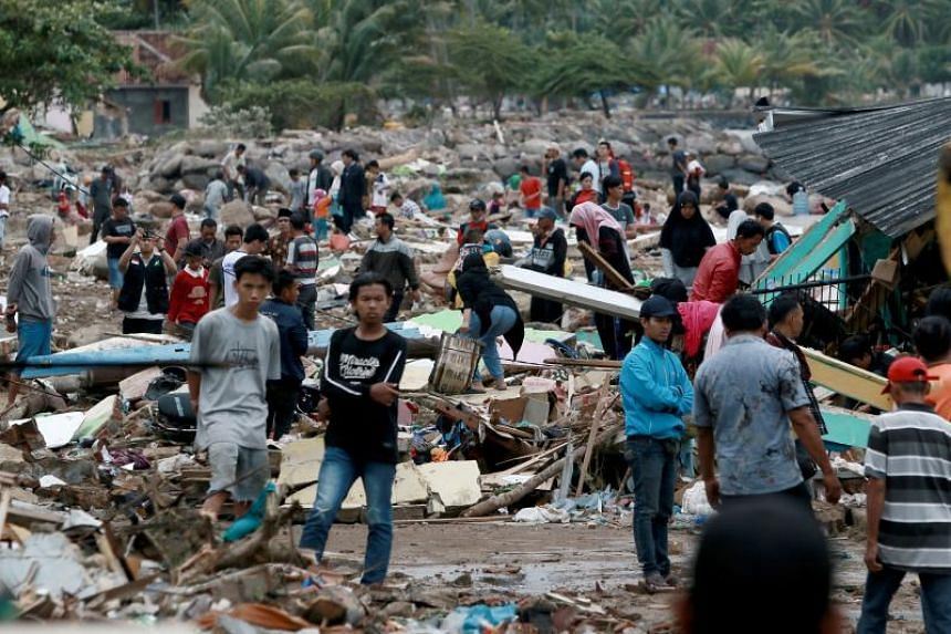 Rescuers and residents search for survivors along the coast in South Lampung on South Sumatra on Dec 23, 2018. The area was hit by a tsunami on Dec 22 following an eruption of the Anak Krakatoa volcano.  .