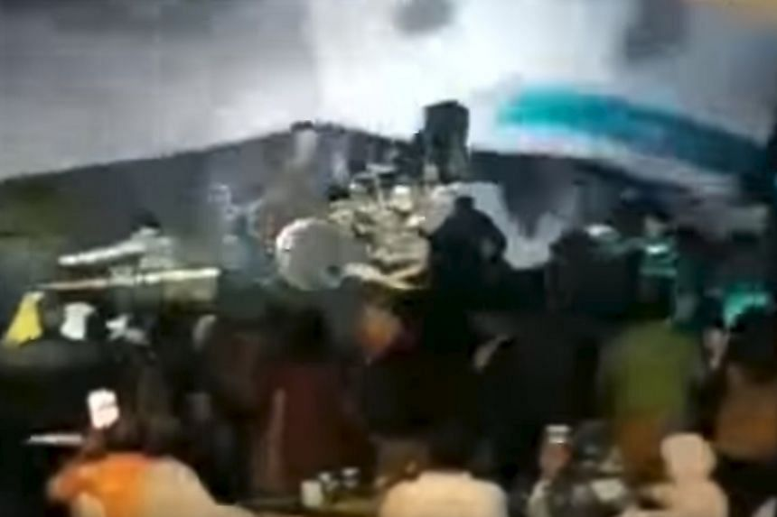 MetroTV footage showing a crowd watching rock band Seventeen perform on the stage before waves caused it to collapse.