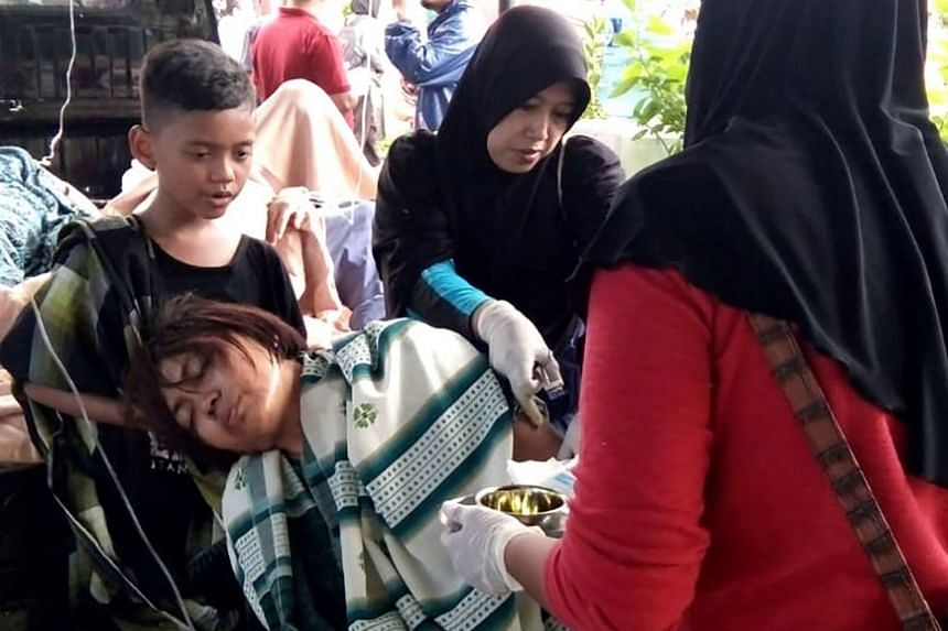 A survivor being attended to outside a hospital in Carita, in Pandeglang regency, yesterday.