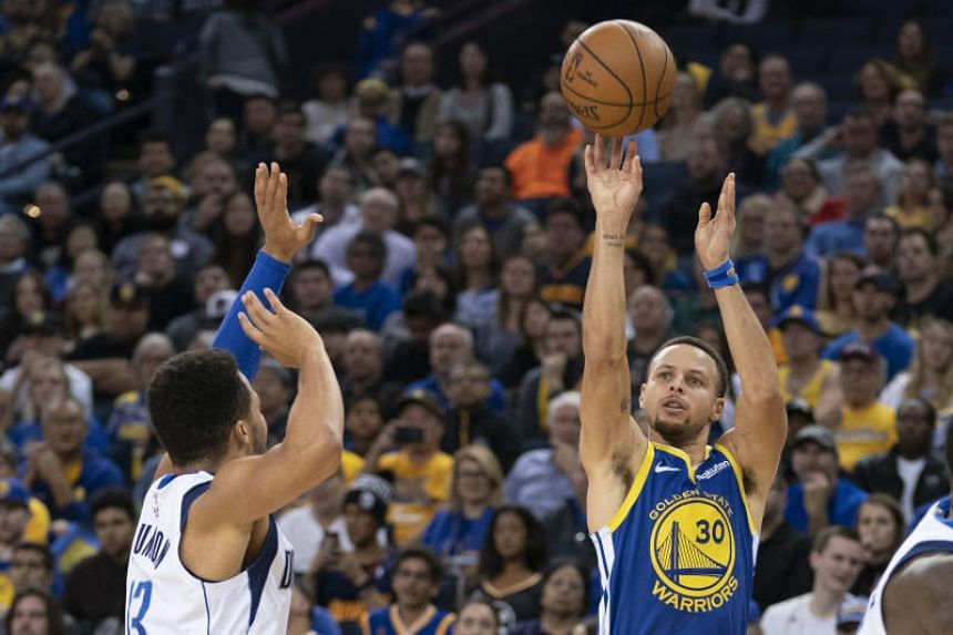 Golden State Warriors guard Stephen Curry (right) shoots against Dallas Mavericks guard Jalen Brunson during the fourth quarter at Oracle Arena on Dec 23, 2018.