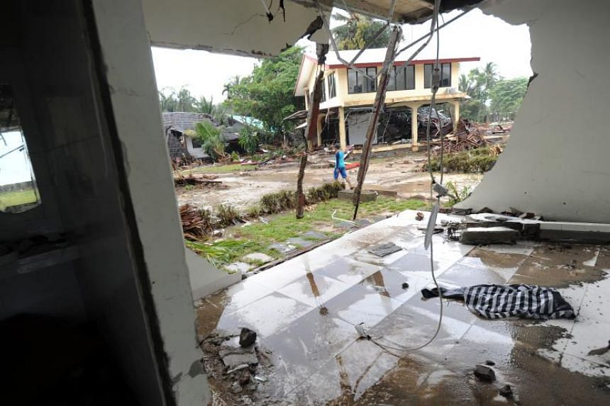 A man walks between damaged buildings at the Mutiara Carita Cottages in Carita, Banten province, on Dec 24, 2018, two days after a tsunami.