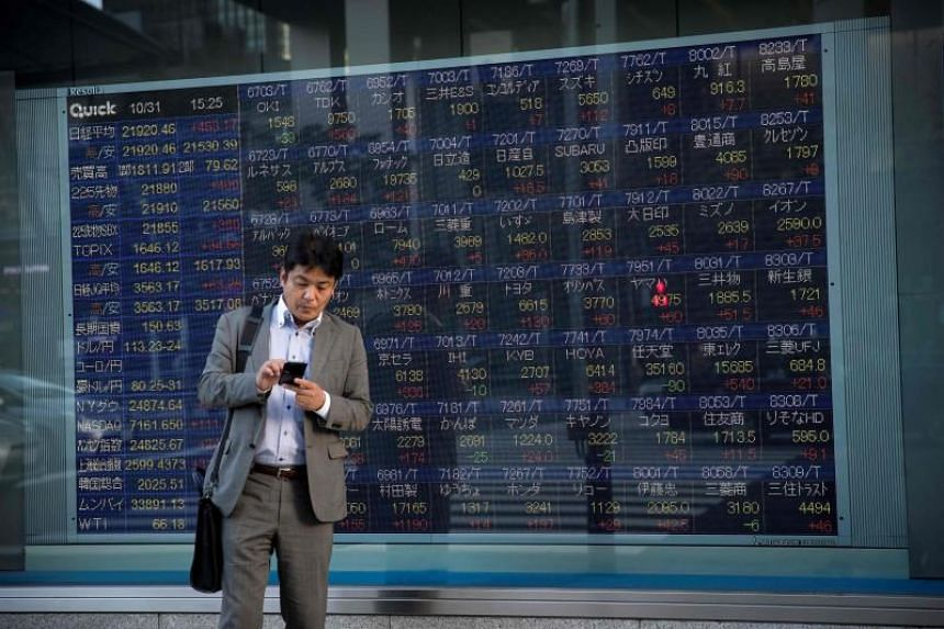 A man checks his smartphone in front of an electronic stock indicator displaying share prices of the Tokyo Stock Exchange in Tokyo, on Oct 31, 2018.