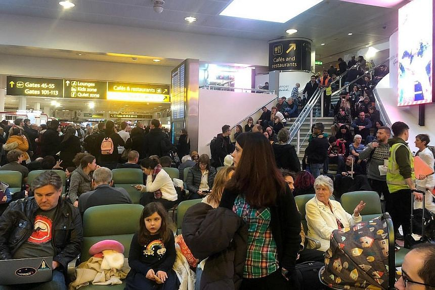 Stranded passengers at Gatwick Airport during the airport runway's closure last week over the disruption caused by drones. The chaos affected more than 140,000 passengers in Britain and reverberated around the world. A man and a woman (below) were in