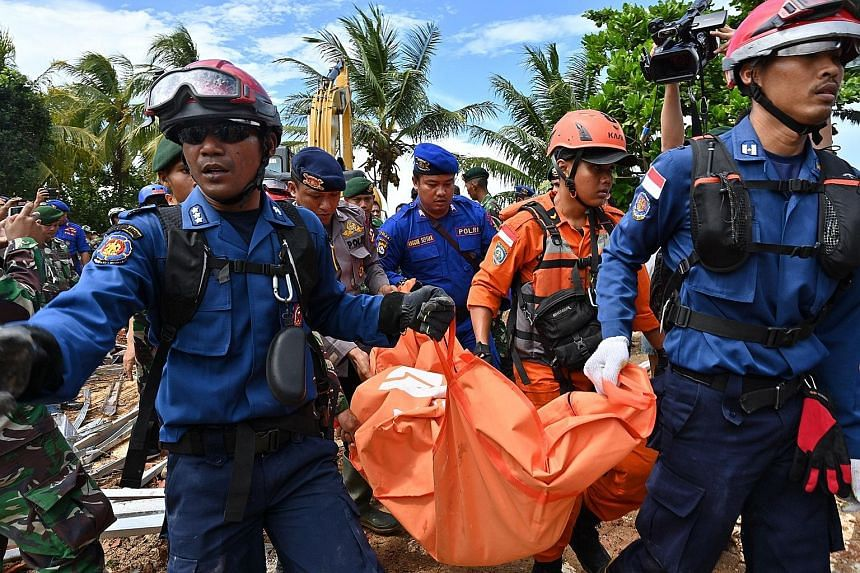A rescue worker and a search-and-rescue dog looking for victims trapped under the rubble at a resort in Tanjung Lesung, Banten province, yesterday. Members of an Indonesian search and rescue team carrying a body bag taken from the Villa Stephanie res