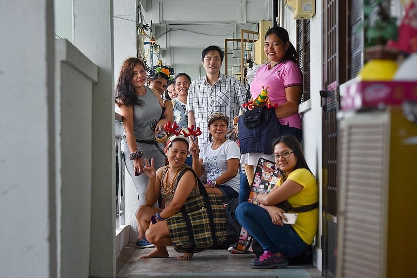 Mr Colin Lau, founder of Freegan in Singapore, with some of the maids who attended the giveaway party. To date, he has held 136 such events at his flat, where the maids are free to take any items he and some members of his group have found.
