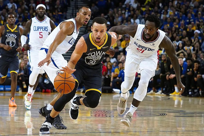 Golden State Warriors star Stephen Curry dribbling past Los Angeles Clippers guards Avery Bradley and Patrick Beverley (No. 21) on Sunday. Curry scored 42 points, including the game winner with half a second left, to help the Warriors overcome a hist
