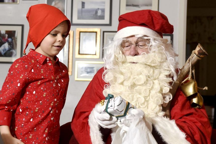 A man dressed as Santa Claus visits a family on Christmas Eve in Espoo, Finland, on Dec 24, 2018.
