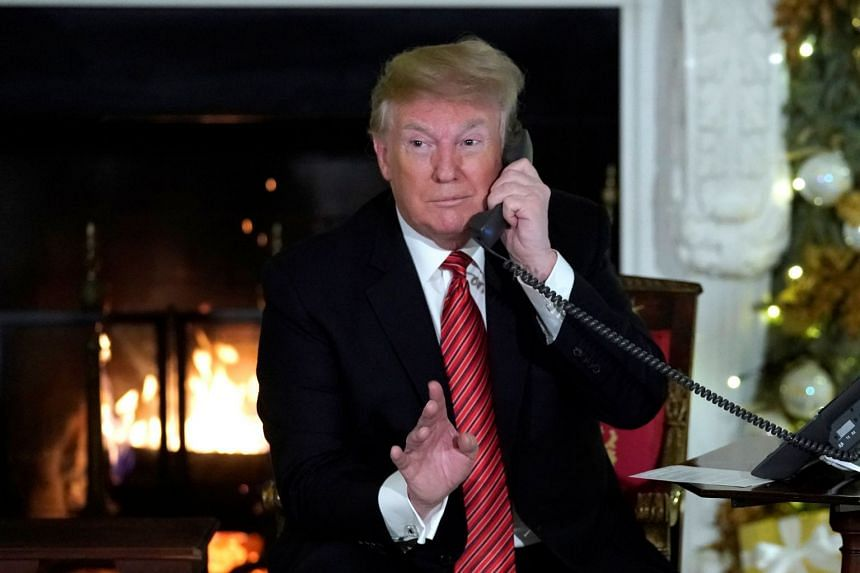 US President Trump participates in NORAD Santa tracker phone calls from children, in the State Dining Room of the White House in Washington.