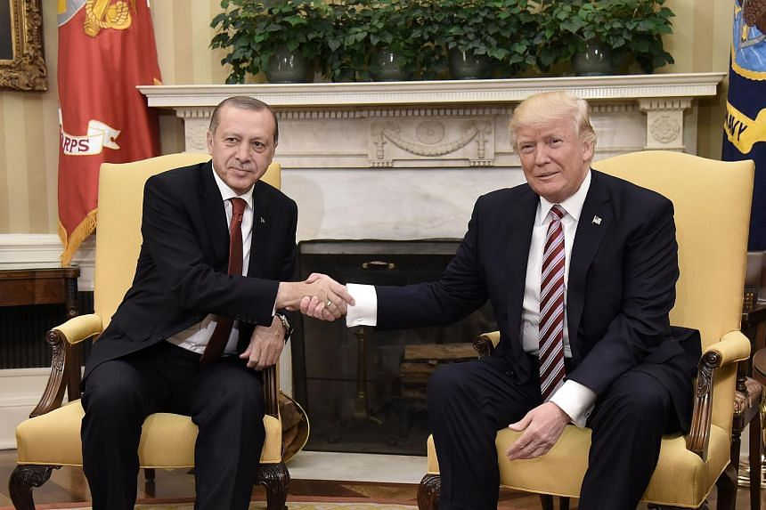 US President Donald Trump (right) shakes hands with Turkish President Recep Tayyip Erdogan during a meeting in the Oval Office of the White House in Washington, DC on May 16, 2017.