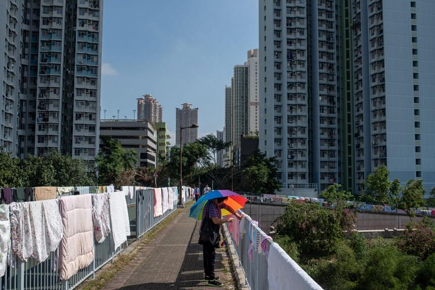 A woman uses an umbrella to shield herself from the sun in the Tin Shui Wai district in Hong Kong, on Dec 1, 2018.