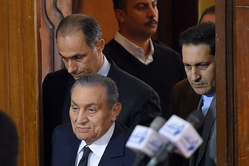 Former Egyptian president Hosni Mubarak (centre) arrives at court, accompanied by his two sons Gamal (left) and Alaa (right).