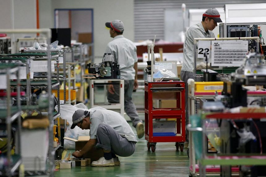 File photo showing workers at a circuit board assembly factory in Singapore. Industry output expanded by 5.3 per cent year on year in November.
