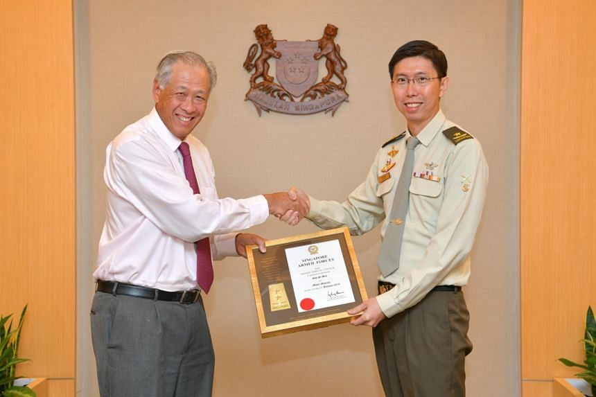 Minister for Defence Ng Eng Hen presenting the promotion certificate to Chief of Army, Brigadier-General Goh Si Hou, at Mindef on Dec 26, 2018.