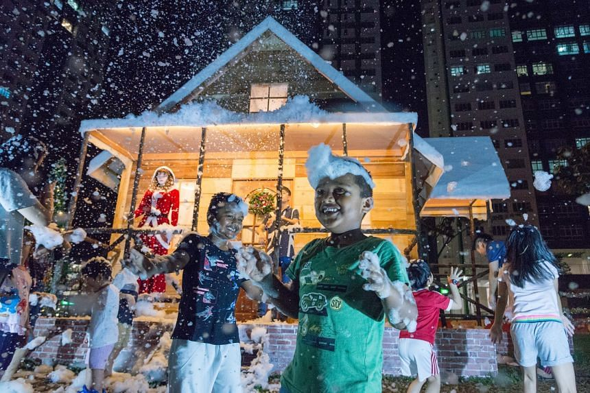 """Children enjoying the foam """"snow"""" on Christmas Day at a neighbourhood in Woodlands. The decorations, which include a snowy log cabin, were put up by carpenter Tan Koon Tat."""