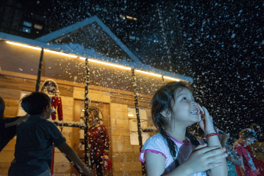"""A child enjoys the foam """"snow"""" on Christmas Day at a neighbourhood in Woodlands. The decorations, which include a snowy log cabin, were put up by carpenter Tan Koon Tat."""