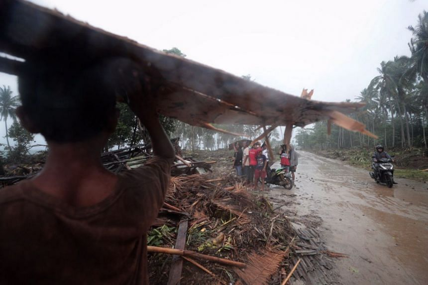 Villagers taking shelter during a sudden downpour as they help in the search for bodies in Cikujang village located in Banten, Indonesia, on Dec 25, 2018.