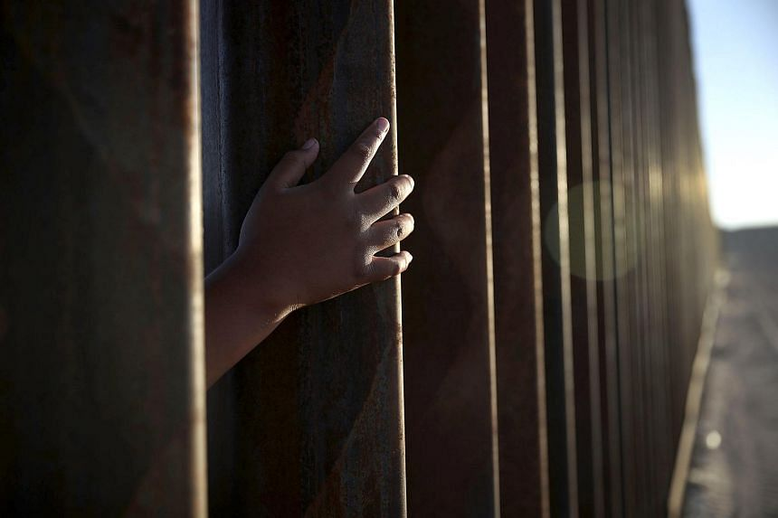 A generic photo of a child reaching through from the Mexican side of the US-Mexico border fence. Two migrant children have died this month after being detained at the border between Mexico and the United States.