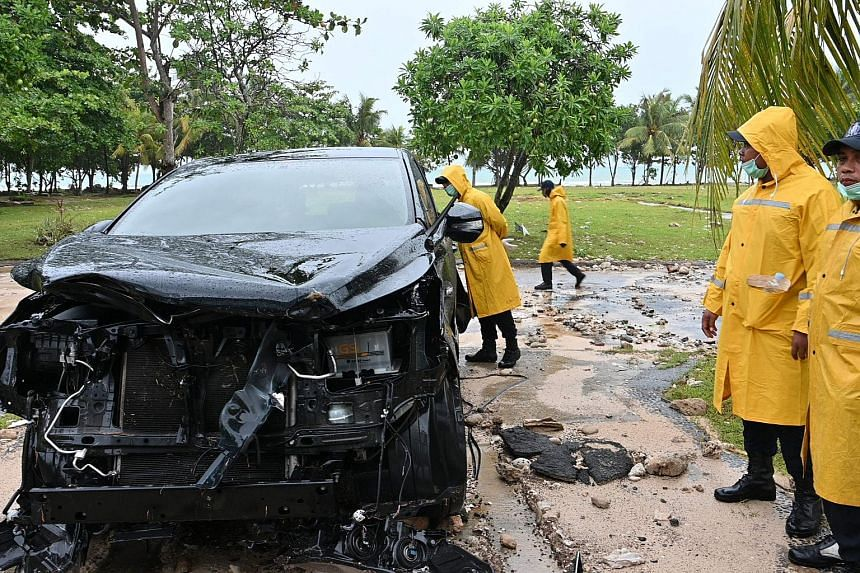 Indonesian internal security personnel examine a damaged car at the Tanjung Lesung Beach resort in the Banten province, on Dec 26, 2018.