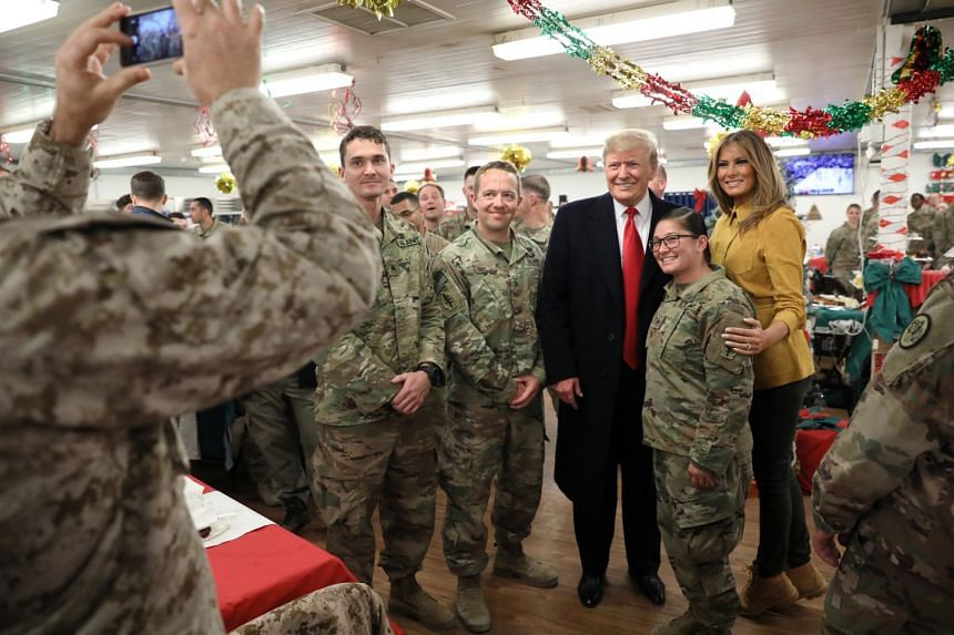 Donald and Melania Trump greet military personnel at Al Asad Air Base.