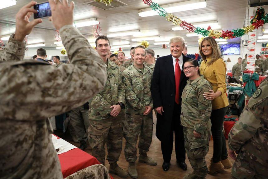 Donald and Melania Trump greet military personnel at Al Asad Air Base.