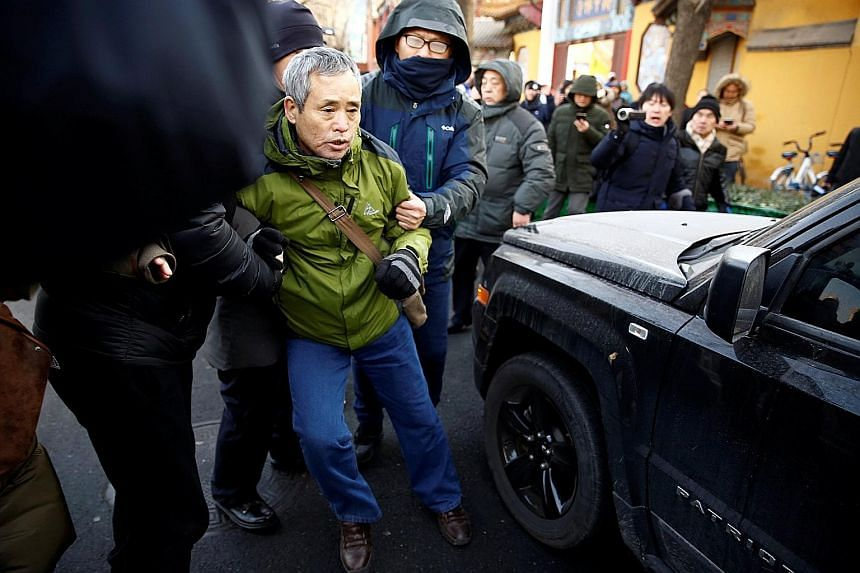 A supporter of prominent rights lawyer Wang Quanzhang (above), who went missing in August 2015 during a crackdown on rights activists, being detained yesterday outside the Tianjin courthouse where Wang's trial was held.