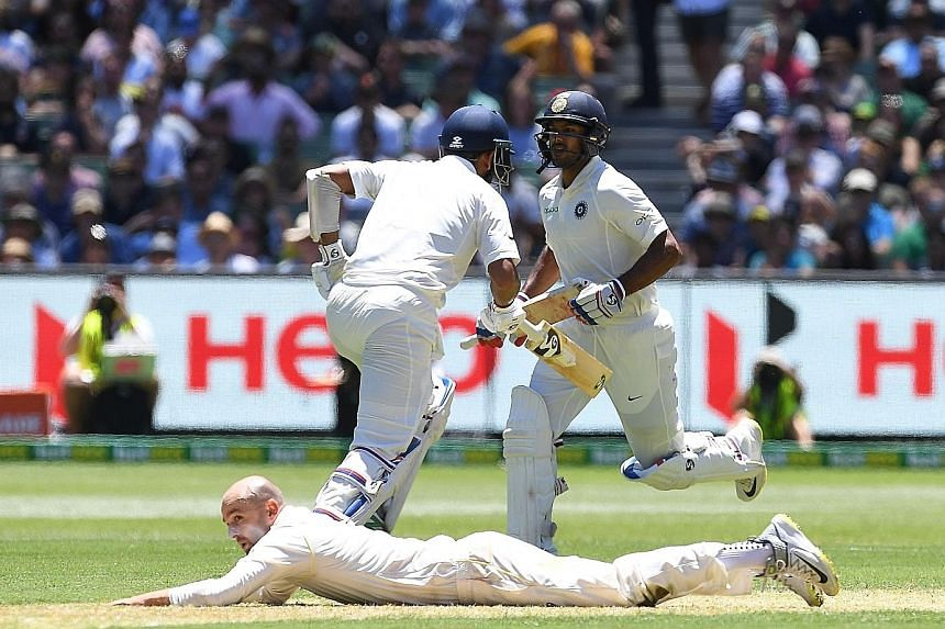 Indian batsmen Cheteshwar Pujara (left) and Mayank Agarwal running between the wickets as Australian fielder Nathan Lyon misses a catch on day one of the Boxing Day Test match at the MCG yesterday. The four-match series is tied 1-1.