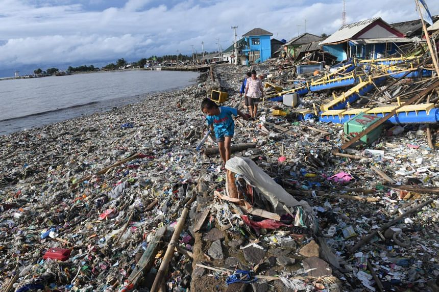 Residents walk among debris after the tsunami at Labuan in Pandeglang, Banten province, Indonesia, on Dec 26, 2018.