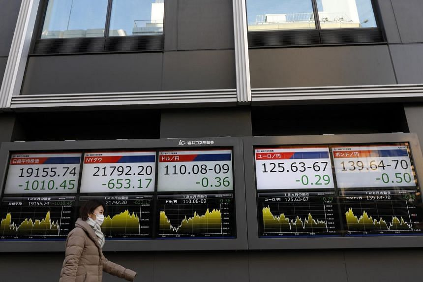 A pedestrian walks past a stock market indicator board showing the Nikkei 225 Stock Average in Tokyo, Japan, on Dec 25, 2018.