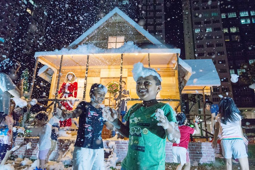 Children playing with snow foam (above) from snow machines that carpenter Tan Koon Tat installed together with the 4.5m-tall log cabin (below) he built in front of Block 178 Woodlands Street 13. Mr Tan said he built the log cabin using materials sour