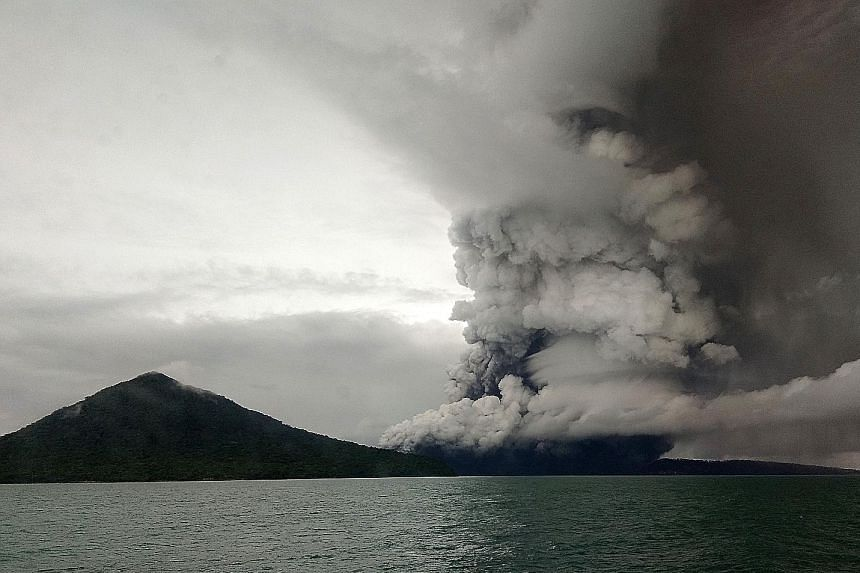 The Anak Krakatau volcano erupting, as seen from a ship on the Sunda Strait on Wednesday. Flights were re-routed as the rumbling volcano spewed columns of ash skywards as high as 3km.