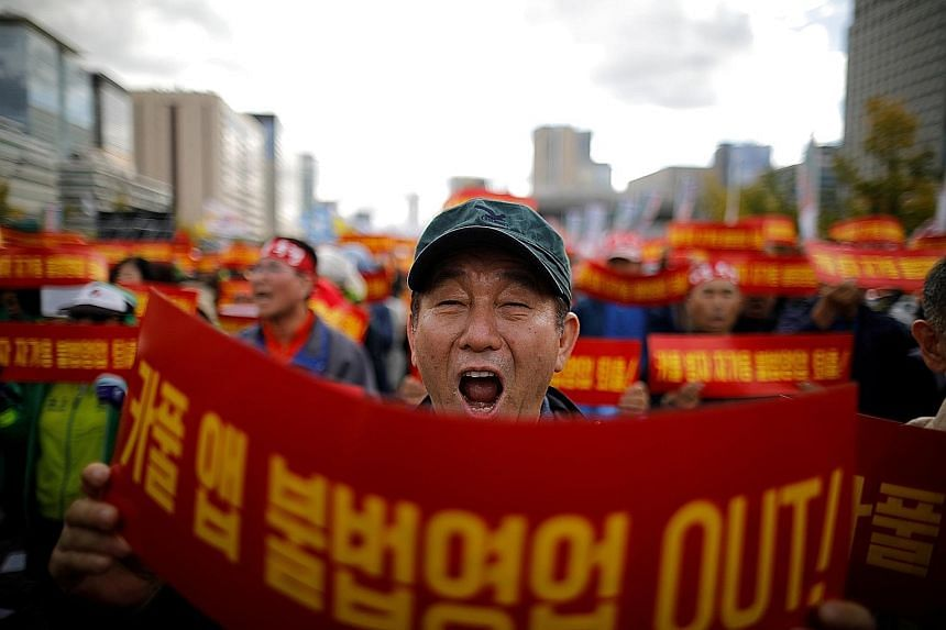 "A taxi driver in South Korea protesting in October against a carpool service application to be launched by Kakao Corp later in the year. The banners read: ""Stop carpool service application, it is illegal business."" Such protests have made it hard for"
