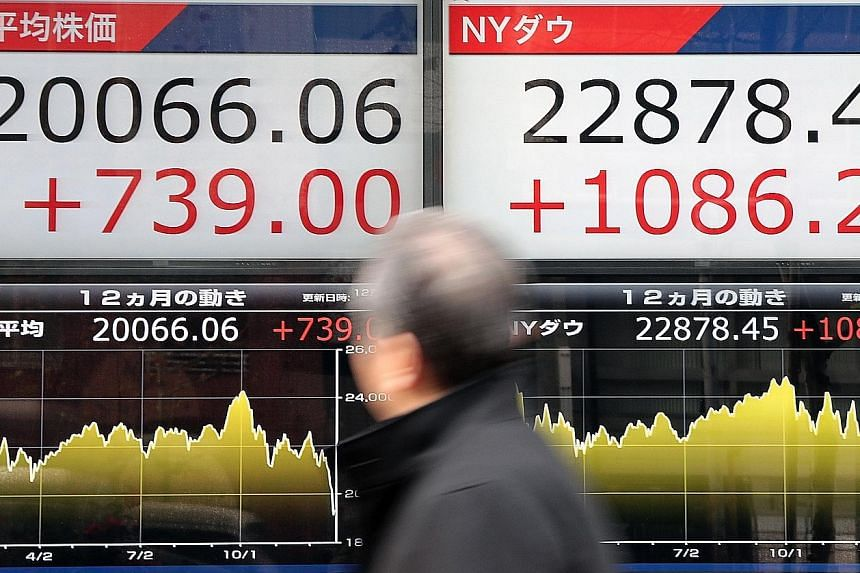 A stock market indicator board showing the Nikkei 225 Stock Average (left) and the New York Dow Jones in Tokyo yesterday. The Dow's rebound helped pull Japan's index out of the bear market it had entered earlier this week, with the Nikkei up nearly 4