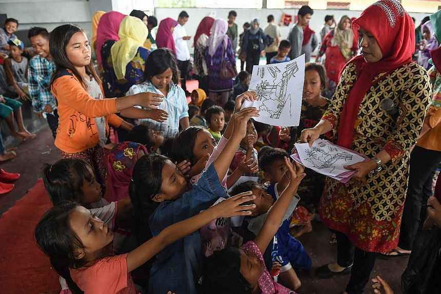 A volunteer distributing drawings for children to colour at a relief centre in Kalianda, in Lampung province, yesterday. Volunteers have been looking out for signs of distress, with some children eating little and struggling to sleep.