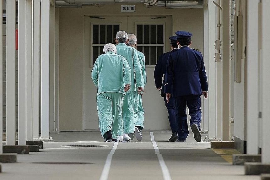 Prison guards escorting inmates along a marked pathway at Sasebo Prison in Nagasaki prefecture. The Justice Ministry's annual White Paper on crime noted that 19 per cent of elderly men and 34 per cent of elderly women reoffended within two years of b