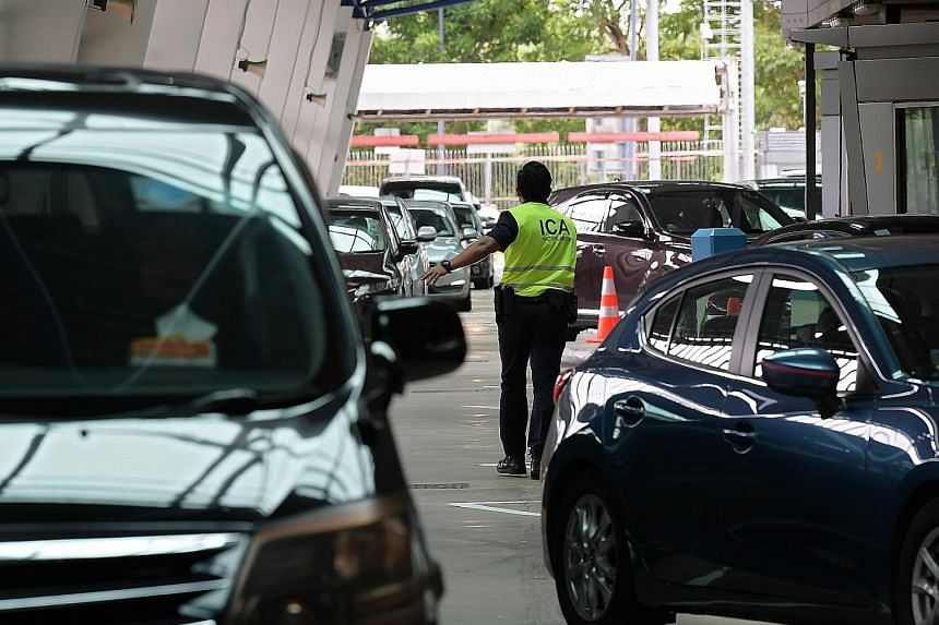 An Immigration and Checkpoints Authority officer directing traffic at the Woodlands Checkpoint yesterday. Home Affairs Minister K. Shanmugam said the situation at the Tuas and Woodlands checkpoints is monitored constantly, and ICA officers are redepl