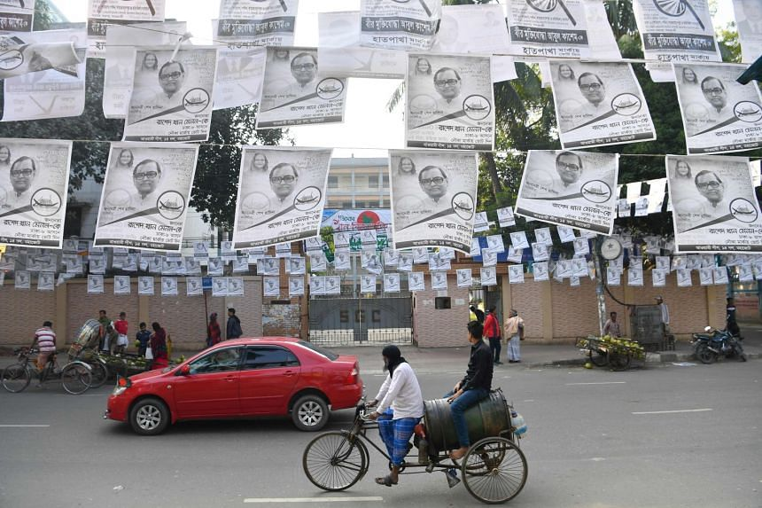 A rickshaw driver cycles past a street adorned with election posters in Dhaka, ahead of the Dec 30 general election, on Dec 28, 2018.