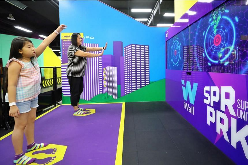 Ms Lynn Lee, 42, and her daughter Leia Leong, nine, playing an interactive parkour game at SuperPark Singapore on Dec 19, 2018.