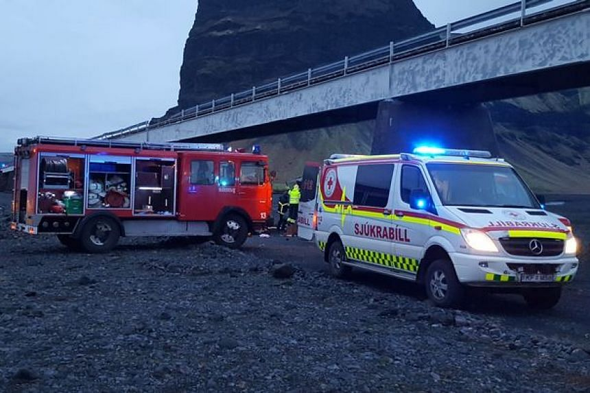 Rescuers assist after a jeep carrying seven people plunged off a bridge into a dry river bed in Iceland.