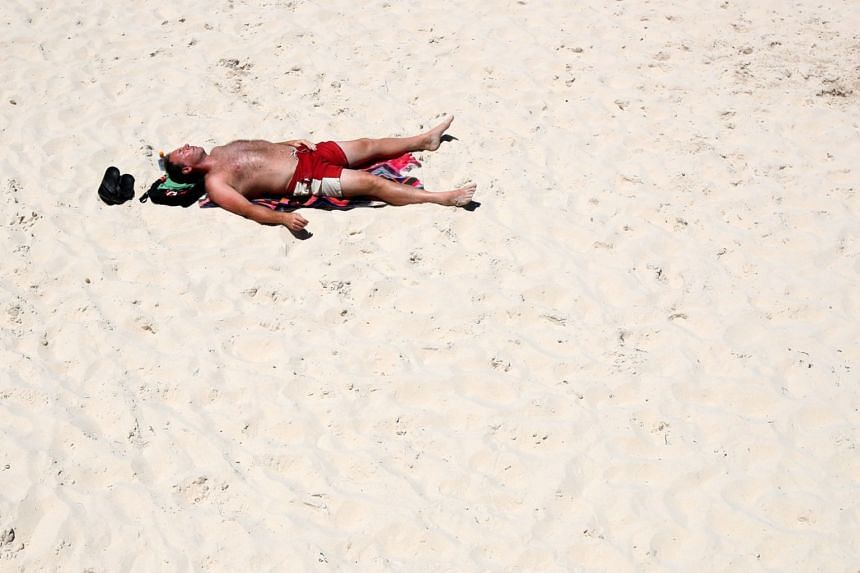 A man lying on Glenelg beach during hot weather in Adelaide, South Australia, on Dec 26, 2018.
