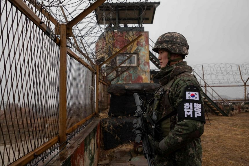 A South Korean soldier stands before a security fence at a guard post at the Demilitarized Zone, on Dec 3, 2018.