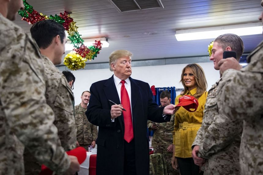 US President Donald Trump signing a cap with First Lady Melania as they greet members of the US military in a dining hall during an unannounced trip to Al Asad Air Base, Iraq, on Dec 26, 2018.