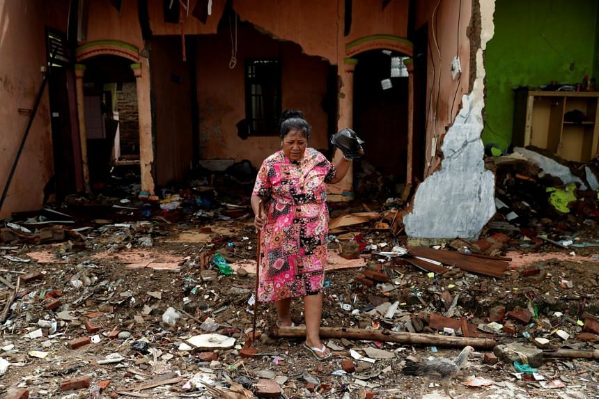 A woman walks among debris at an area affected by the tsunami in Labuhan, Banten province, Indonesia, Dec 27, 2018.