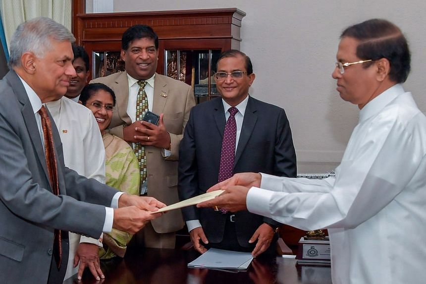 Sri Lankan President Maithripala Sirisena (right) handing over official documents to Mr Ranil Wickremesinghe at his reinstatement as prime minister on Dec 16.