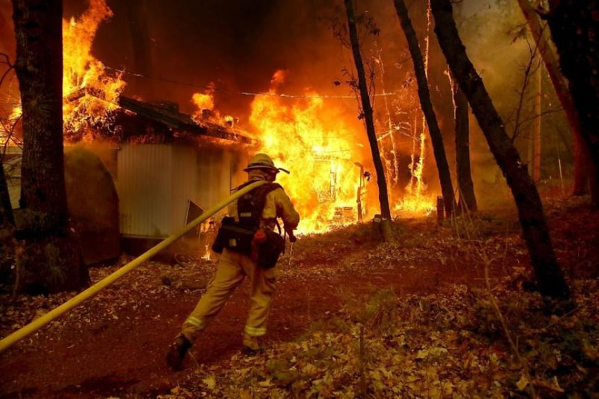 A firefighter pulls a hose towards a burning home as a wildfire moves through the area in Magalia, California, on Nov 9, 2018.