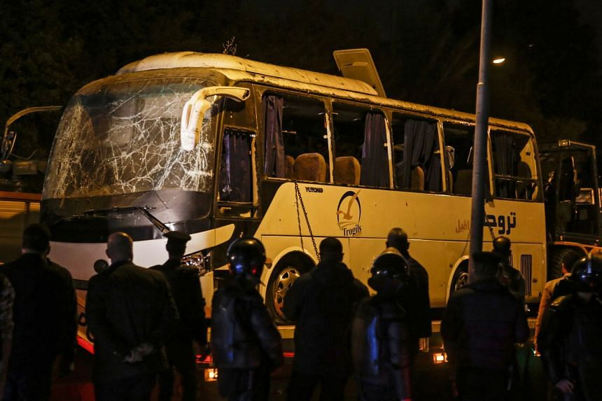 Security personnel stand guard during the removal of a tourist bus hit by a roadside bomb in Egypt.