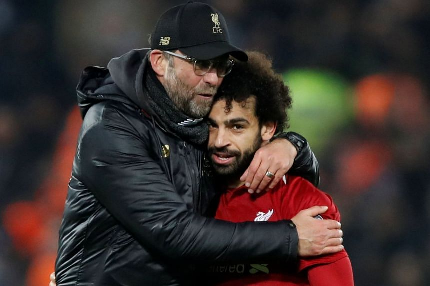 Liverpool manager Juergen Klopp celebrates with Salah at the end of a match.