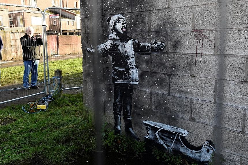 One side of the work shows a child seemingly playing in the snow (above), but the other side shows smoke rising from a burning fire and the snowflakes are actually falling ash.