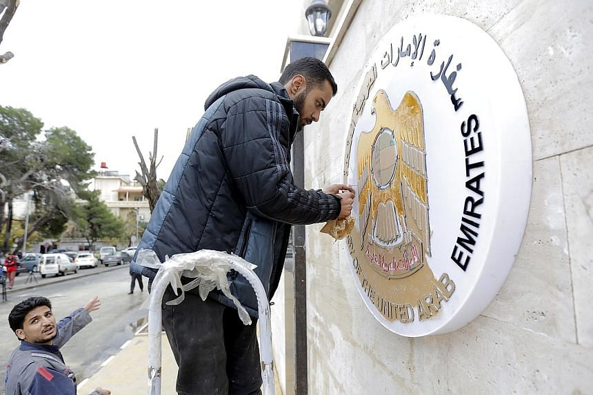 Workers cleaning the metal plaque outside the United Arab Emirates embassy in Damascus, Syria. According to an Emirati statement, an acting charge d'affaires has already started working and the UAE was keen to put relations back on their normal track